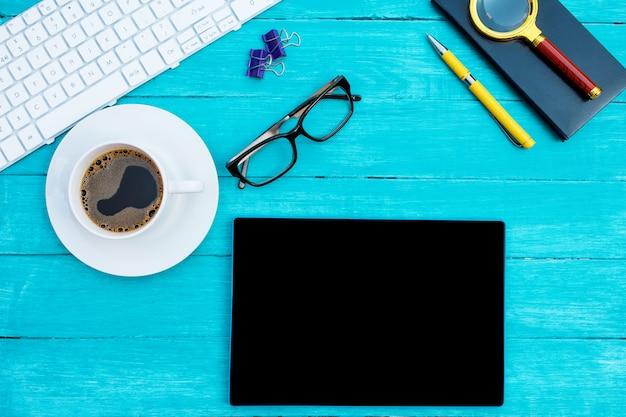 Biała filiżanka kawy, biała klawiatura, czarny notatnik, czarne okulary i tablet na turkusowym drewnianym biurku