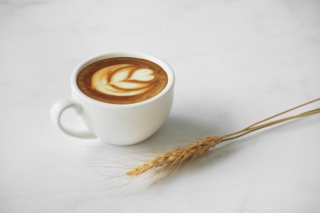 Biała filiżanka kawy. białe marmurowe tło.