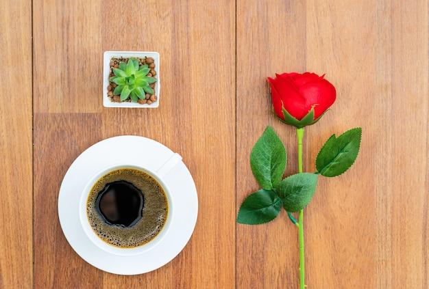 Biała filiżanka kawy i czerwona róża walentynki koncepcja
