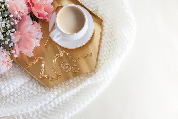 Biała filiżanka kawy i dekoracje na złotej tacy w stylu nordyckim. różowe piwonie. na skórzanej sofie leży biała pled.