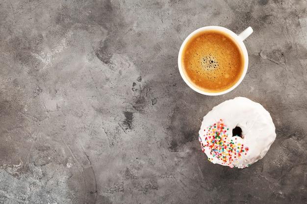 Biała filiżanka kawy i pączek w białym lodowaceniu i stubarwnej cukrowej ciasta polewie na szarym tle. leżał płasko. skopiuj miejsce