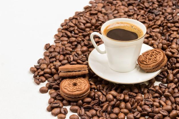 Biała filiżanka kawy i ziaren na białym tle