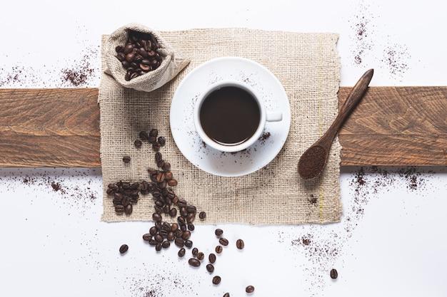 Biała filiżanka kawy i ziarna kawy rozlane z torebki