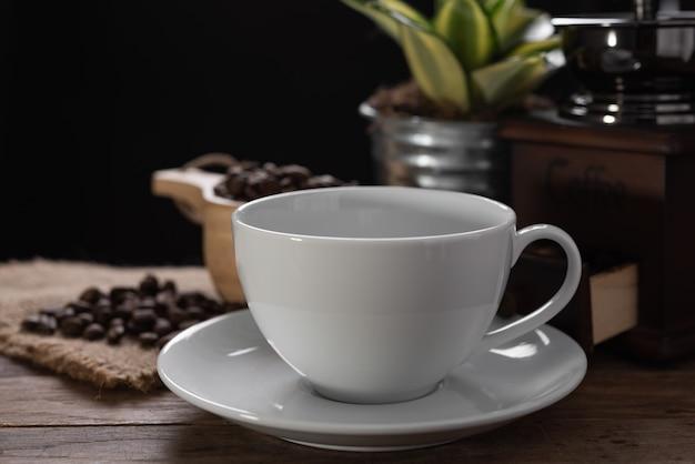 Biała filiżanka kawy, młynek do kawy i palona fasola w szklanym słoju na drewnianym stole z ciemnością