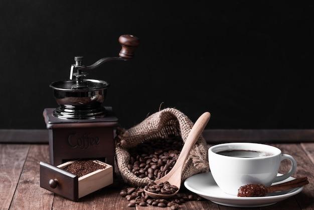 Biała filiżanka kawy, młynek do kawy i ziarna kawy w płótnie na stole z drewna
