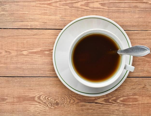 Biała filiżanka kawy na drewnianym stole. widok z góry.