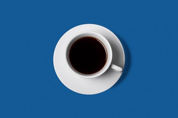 Biała filiżanka kawy na klasycznym niebieskim stole.