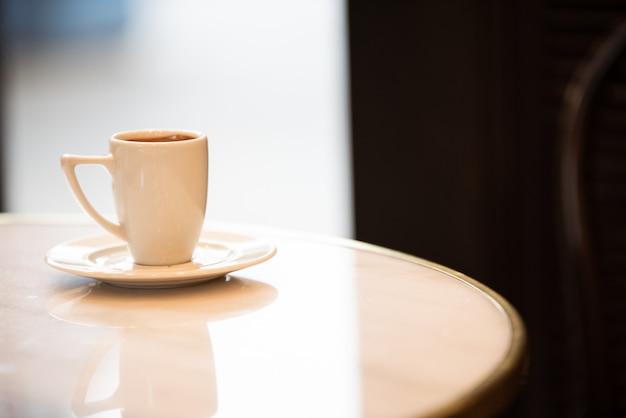 Biała filiżanka kawy na marmurowym stole wewnątrz kawiarni.