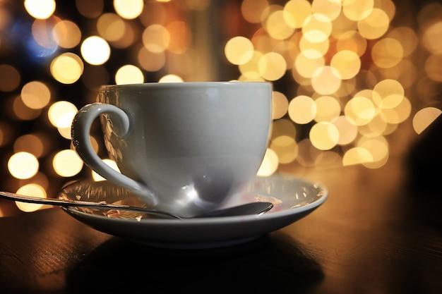 Biała filiżanka kawy na stole na blured tle z okręgiem bokeh