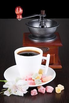 Biała filiżanka kawy po turecku z rozkoszą rahat i młynkiem do kawy na drewnianym stole