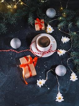Biała filiżanka kawy, prezenty świąteczne i wieczorem girlanda w kształcie choinki na ciemnym stole. domowa wakacyjna atmosfera