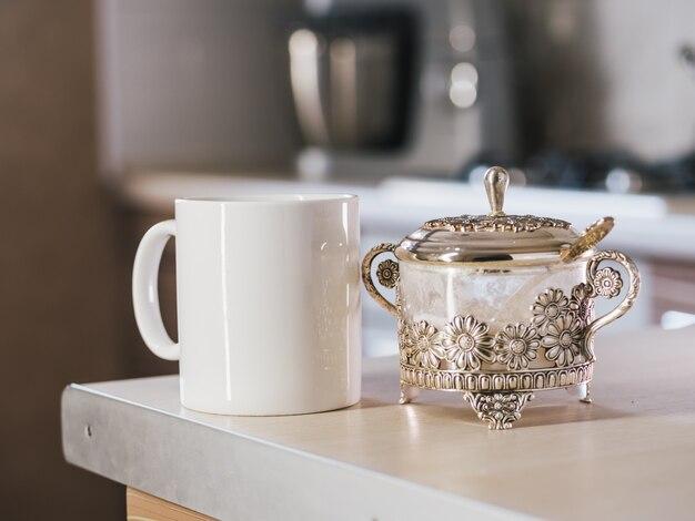 Biała filiżanka kawy z cukrem na stole