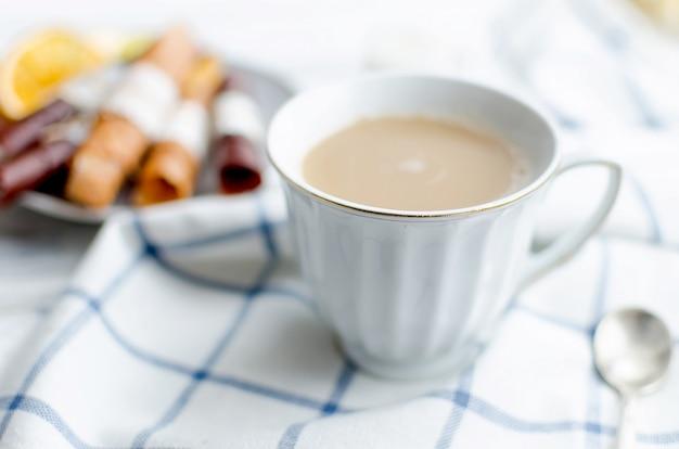 Biała filiżanka kawy z mlekiem, owocową trocią i frytkami