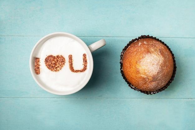 Biała filiżanka kawy z napisem na piance kocham cię i babeczka.