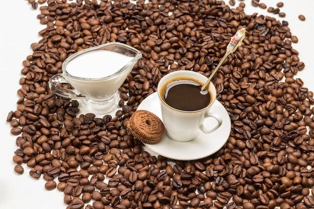 Biała filiżanka kawy z pianką. ciasteczka czekoladowe na spodeczku. szklana śmietanka z kremem. ziarna kawy na stole. białe tło. widok z góry