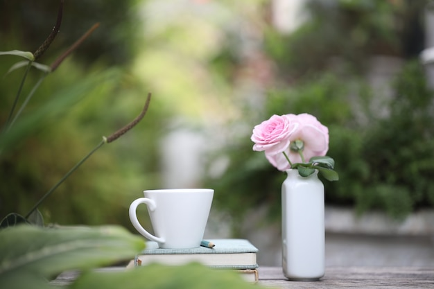 Biała filiżanka kawy z różową różą w ceramicznym wazonie i zeszytach na wyblakłym drewnianym stole na zewnątrz