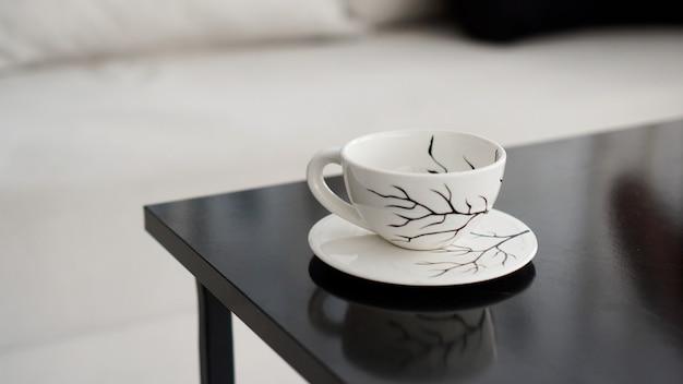 Biała filiżanka kawy z wzorem czarnych gałązek na czarnym stole w pomieszczeniu
