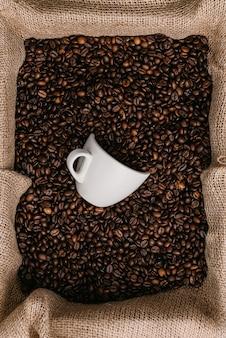 Biała filiżanka leży w palonych ziarnach kawy