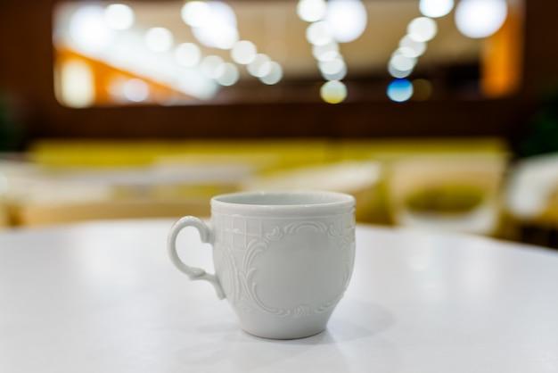 Biała filiżanka na białym stole i zamazanym tle.
