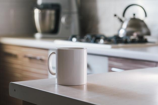 Biała filiżanka na stole w kuchni