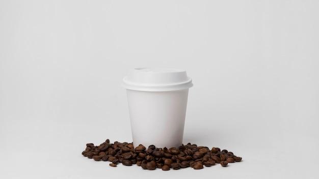 Biała filiżanka na ziarnach kawy