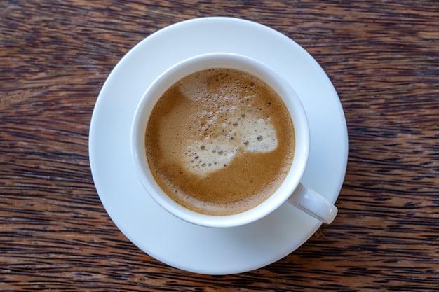 Biała filiżanka świeżej kawy na drewnianym stole, widok z góry, zbliżenie