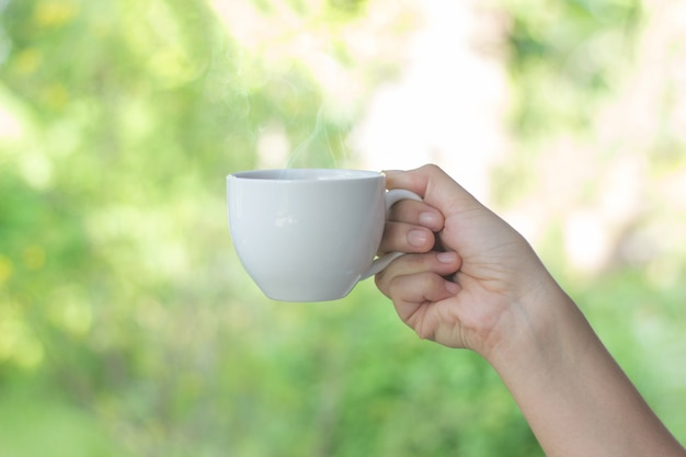 Biała filiżanka w ręce zamazuje tło, młode kobiety pije kawę