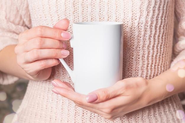 - biała filiżanka w rękach kobiety w różowym zimowym swetrze. świąteczny kubek do kawy.