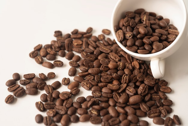 Biała filiżanka wypełniona ziarnami kawy