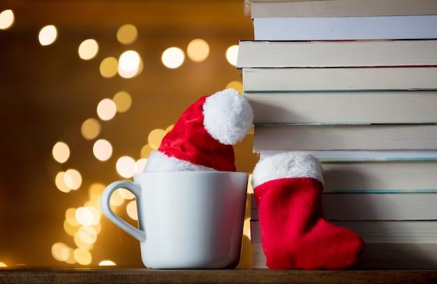Biała filiżanka z bożonarodzeniowym kapeluszem i książkami