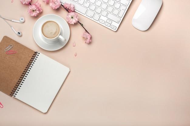 Biała filiżanka z cappuccino, sakura kwiatami, klawiaturą, budzikiem, notatnikiem na pastelowym różowym tle