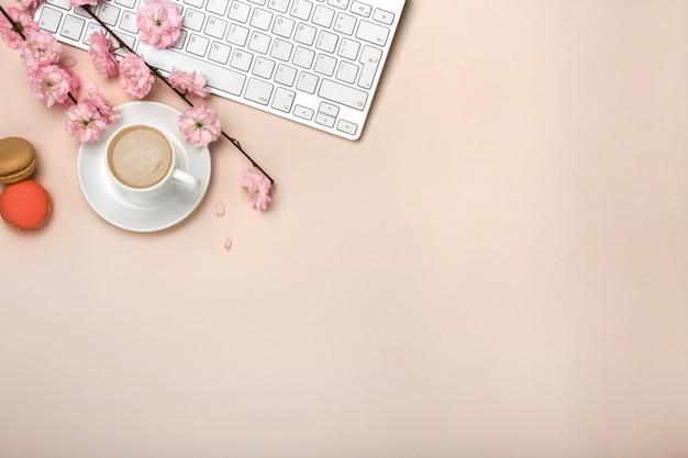 Biała filiżanka z cappuccino, sakura kwiaty, klawiatura na pastelowym różowym tle
