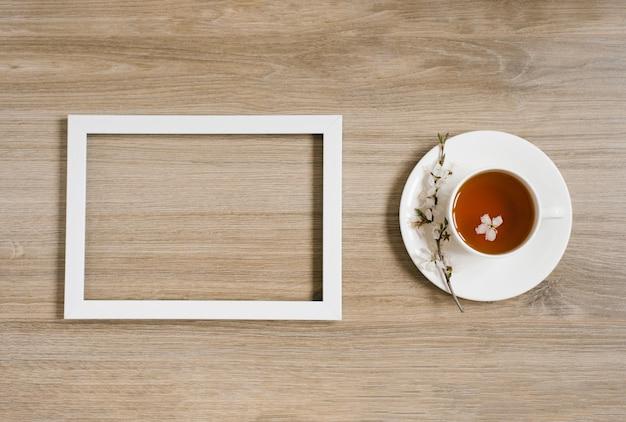 Biała filiżanka z czarną herbatą i gałązką kwiatu jabłoni oraz białą ramką na drewnianym tle. mocap i up prostranstva