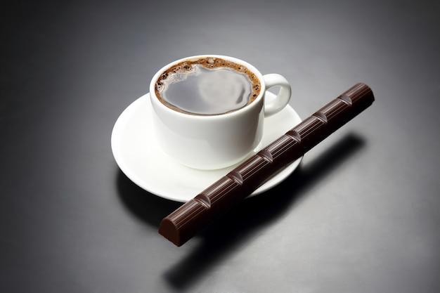 Biała filiżanka z czarną kawą i czekoladą na spodeczku