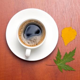 Biała filiżanka z czarną kawą i jesiennymi liśćmi