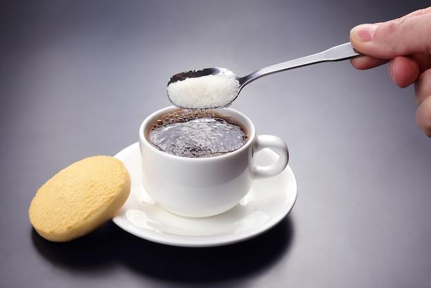 Biała filiżanka z czarną kawą i łyżka z cukrem