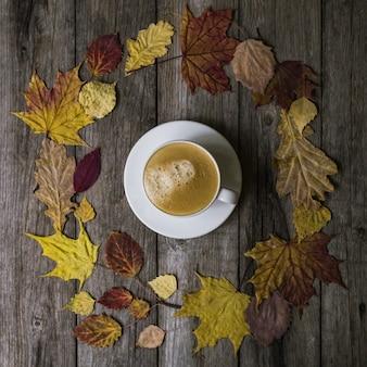 Biała filiżanka z czarną kawą w kręgu barwionych suchych liści na starym drewnianym tle