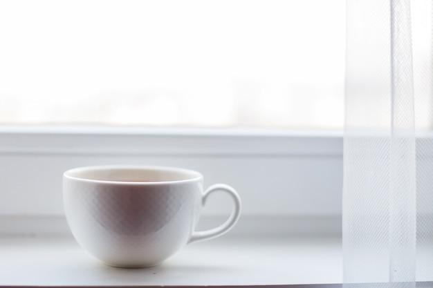 Biała filiżanka z herbatą stoi na parapecie w oknie