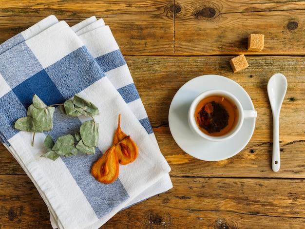 Biała filiżanka z herbatą ziołową. na ręczniku suszona gruszka i eukaliptus.