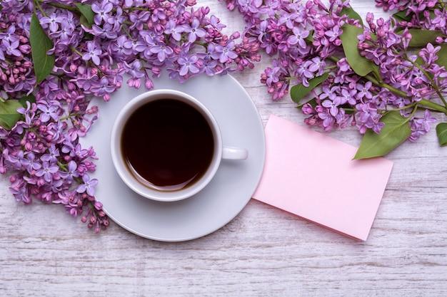 Biała filiżanka z kawą lub herbatą, notatka z życzeniami, bukiet bzów na drewnianym tle. fioletowe wiosenne kwiaty. kompozycja poranna.