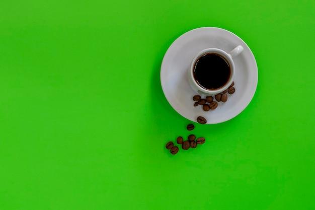 Biała filiżanka z kawą na zielonym panelu.