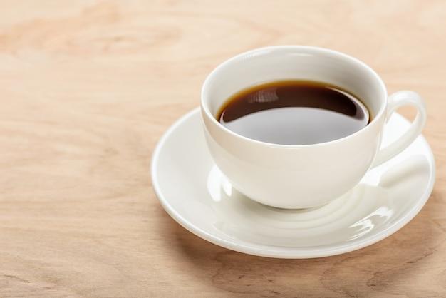 Biała filiżanka z napojem na spodeczku na drewnianym stole.