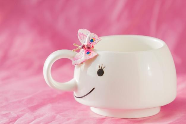 Biała filiżanka z różowym tłem