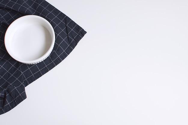 Biała forma do pieczenia i czarna serwetka w kratkę