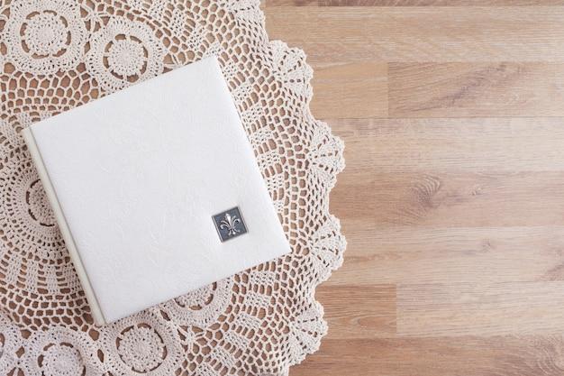 Biała fotoksiążka ze skórzaną okładką. stylowy album na zdjęcia ślubne. rodzinny album fotograficzny na stole. piękny notes lub fotoksiążka z eleganckim ażurowym tłoczeniem na drewnianym tle.