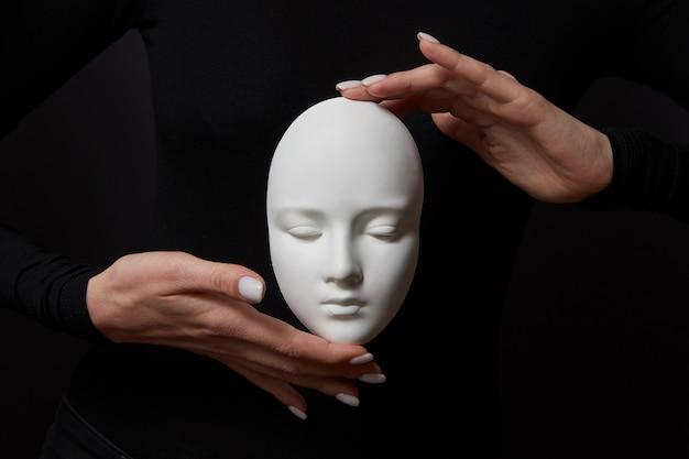 Biała gipsowa maska twarz trzyma palce kobiety na czarnej ścianie, kopia przestrzeń. koncepcja społecznych masek psychologicznych