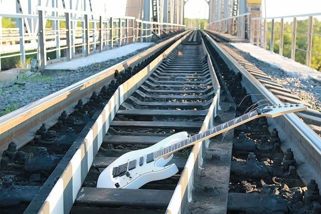 Biała gitara elektryczna na torach kolejowych i industrialny szary kamień