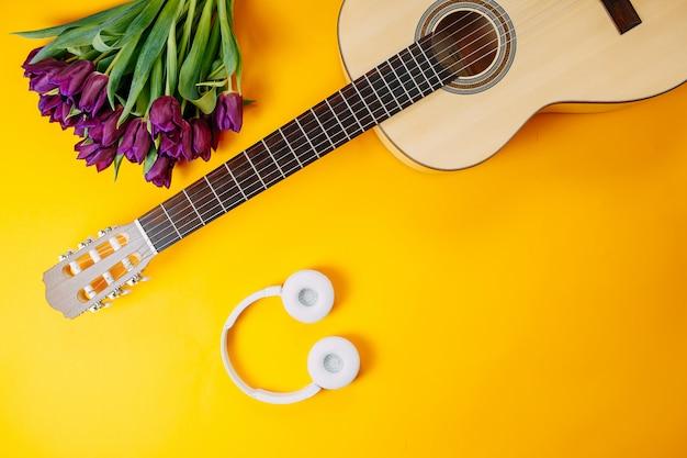 Biała gitara i białe słuchawki bezprzewodowe na pomarańczowym tle, wiosenne kwiaty, bukiet fioletowych tulipanów, biała gitara i kwiaty, plakat z muzyką wiosenną.