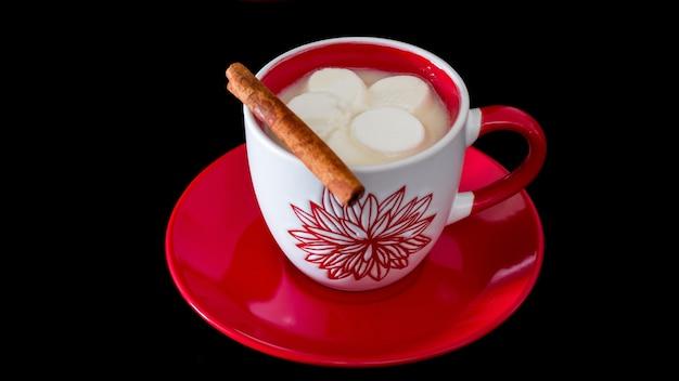 Biała gorąca czekolada, marshmallow i cynamonowy kij na czerwieni talerzu. selektywne skupienie.