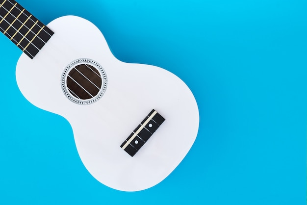 Biała hawajska gitara, ukulele na błękitnym tle. koncepcja muzyczna. szablon flat lay. miejsce na tekst